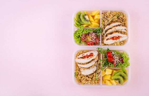 Lunch box with chicken, bulgur, microgreens, tomato and fruit