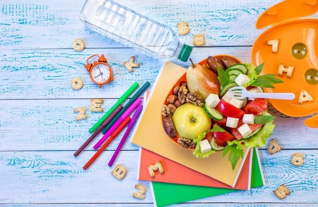 木製の背景に学校の食べ物とランチボックス