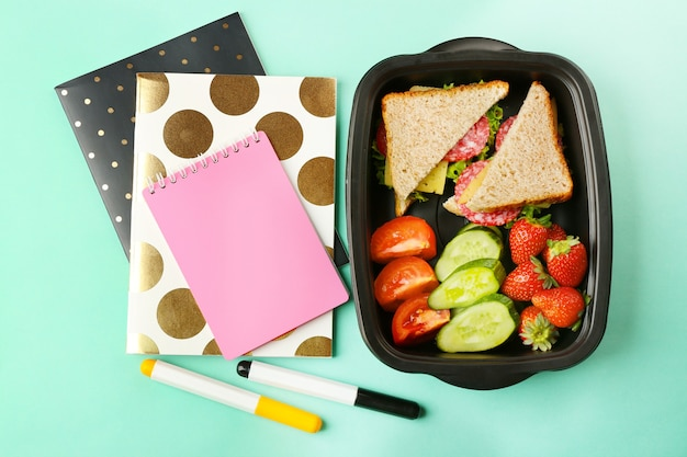 Lunch box with food and stationery on turquoise background
