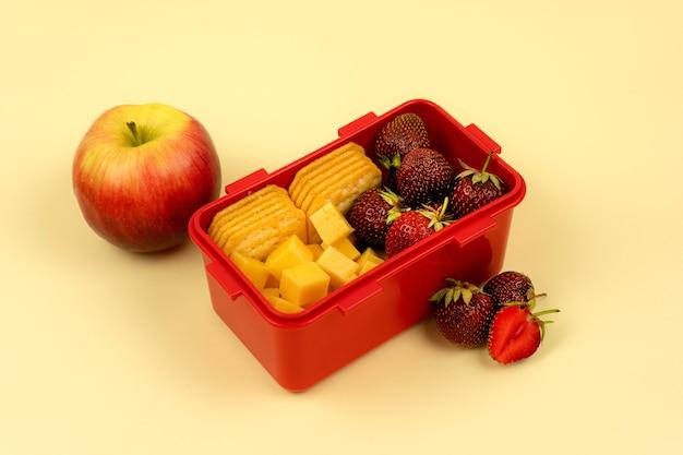 Ланч-бокс с фруктами, печеньем и сыром для быстрого обеда на цветном фоне. здоровая пища.