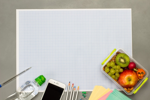 Lunch box with fruits and nuts, blank paper, smartphone and bottle of water