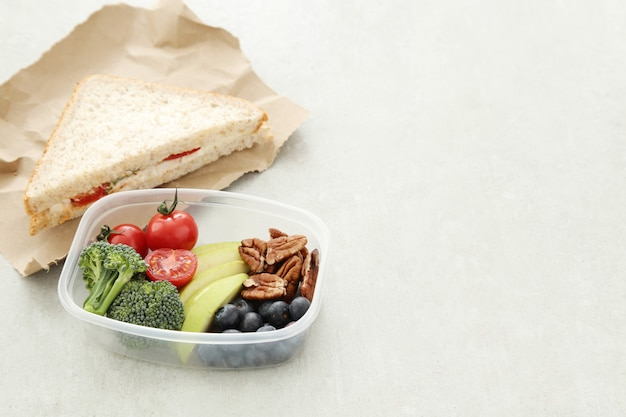 Lunch box with healthy food and sandwich