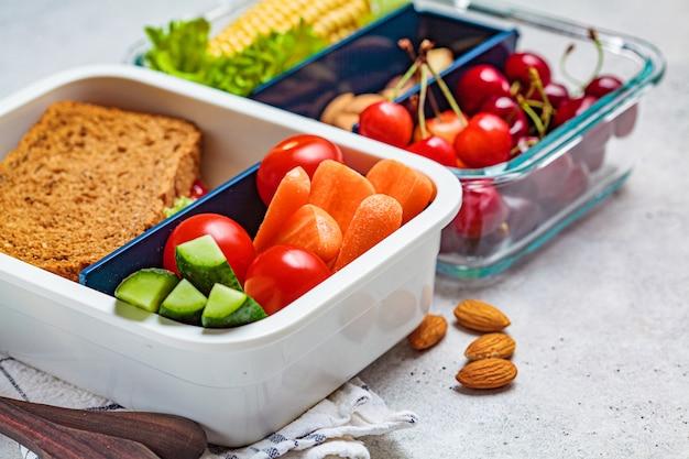 ヘルシーな生鮮食品のお弁当。サンドイッチ、野菜、果物、ナッツ、食品容器、明るい背景。