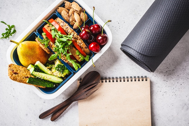 Lunch box with heathy food, notebook and mat on gray