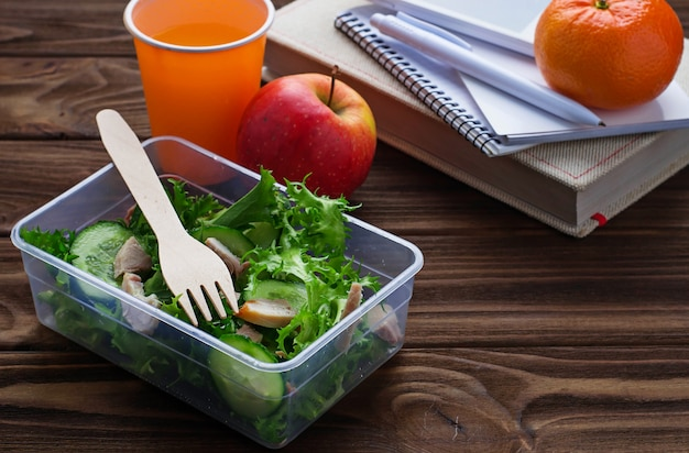 Lunch box with salad, apple, tangerine and juice.