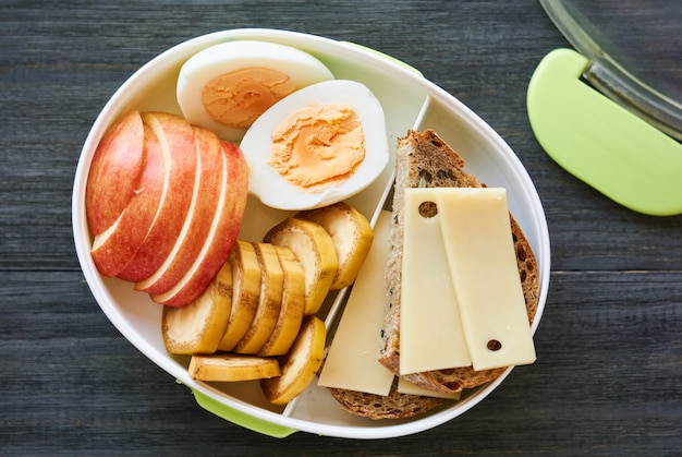 Lunch box with sandwich, egg and fresh fruit