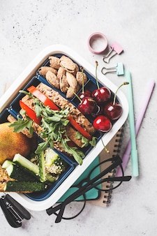 Lunch box with sandwich, fruit, snacks, notebook, pencils and school items, top view.