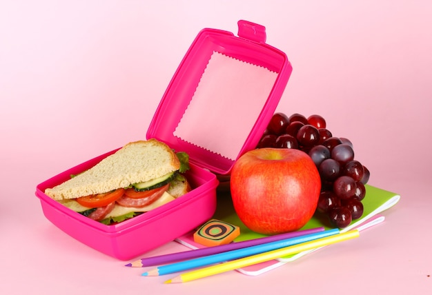 Lunch box with sandwich,fruit and stationery on pink table