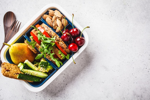 Lunch box with sandwich, pear, vegetables, nuts and snacks on gray