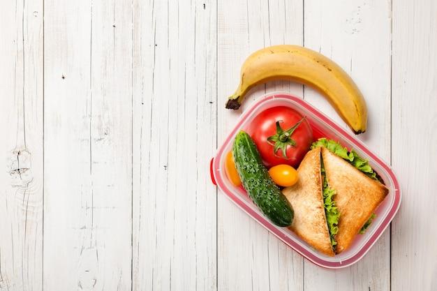サンドイッチ、野菜、バナナのお弁当