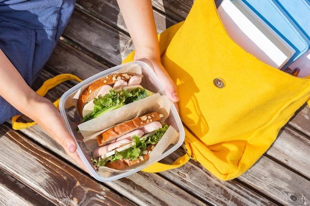 Ланч-бокс с бутербродами в руках ребенка на скамейке, рюкзак со школьными принадлежностями.