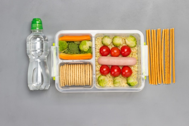 Lunch box with sausage, broccoli and tomatoes, bottle of water and pencils