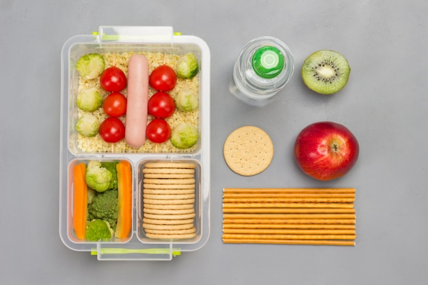 Lunch box with sausage, broccoli and tomatoes.