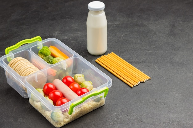 Lunch box with sausage and vegetables, bottle of yogurt and edible straws