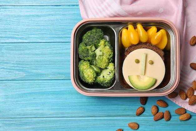 Ланч-бокс с вкусной креативной едой для ребенка на столе