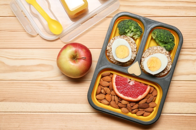 Lunch box with tasty creative food for kid on wooden table