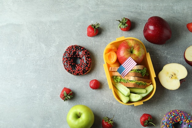 Lunch box with tasty food and american flag on gray textured background