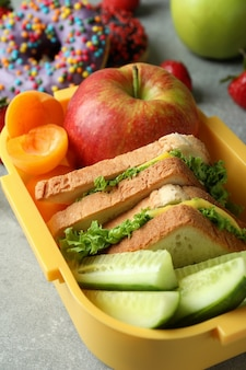 Lunch box with tasty food on gray textured background