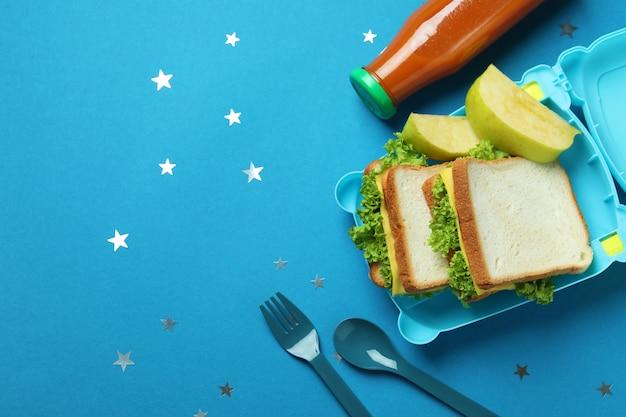 Ланч-бокс с вкусной едой на синем фоне