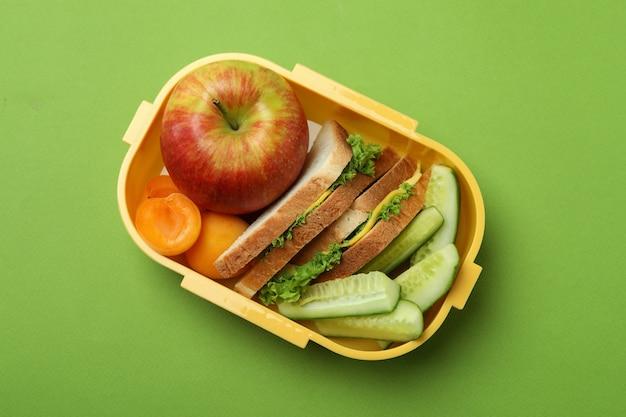 Ланч-бокс с вкусной едой на зеленом фоне
