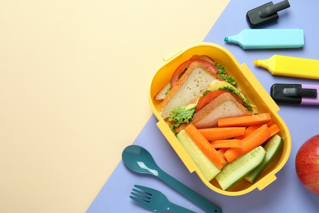 Lunch box with tasty food on two tone background