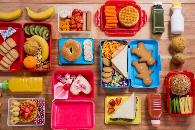 Lunch box with various snack, fruit and sweet food on wooden table