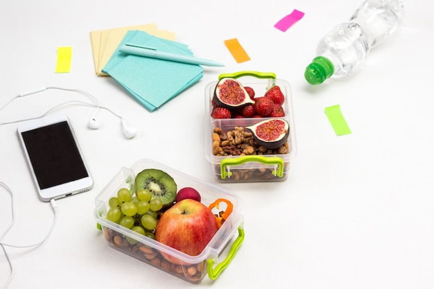Lunch boxes with fruits and nuts on table. smartphone with headphones, paper for notes and bottle of water on white