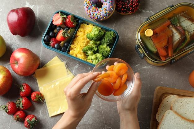 Ланч-боксы с вкусной едой и женскими руками на сером текстурированном столе