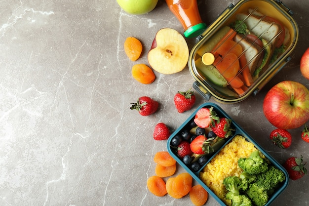 Lunch boxes with tasty food on gray textured table