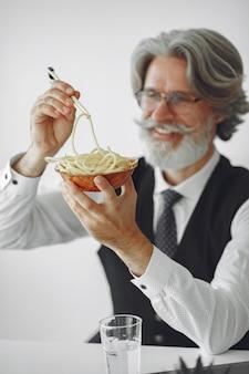 Перерыв на обед. элегантный мужчина в офисе. бизнесмен в белой рубашке. человек ест лапшу.