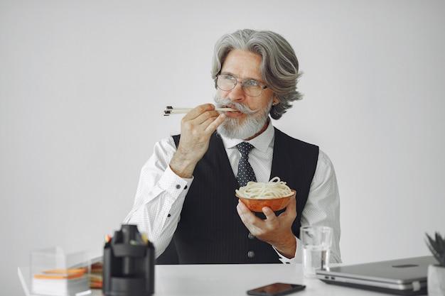 Pausa pranzo. uomo elegante in ufficio. uomo d'affari in camicia bianca. l'uomo mangia le tagliatelle.