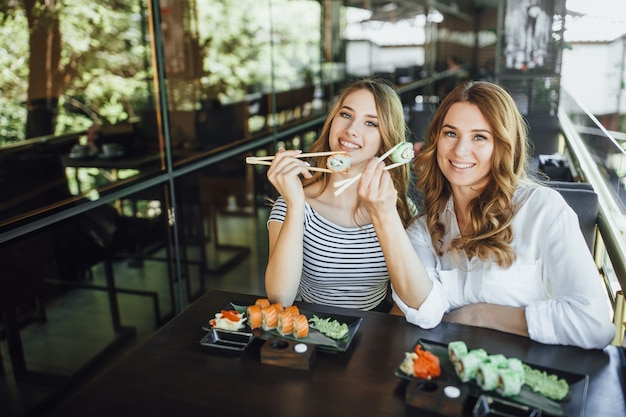 Lunch at a chinese restaurant on the summer terrace. mom and her young beautiful daughter eat sushi with chinese sticks