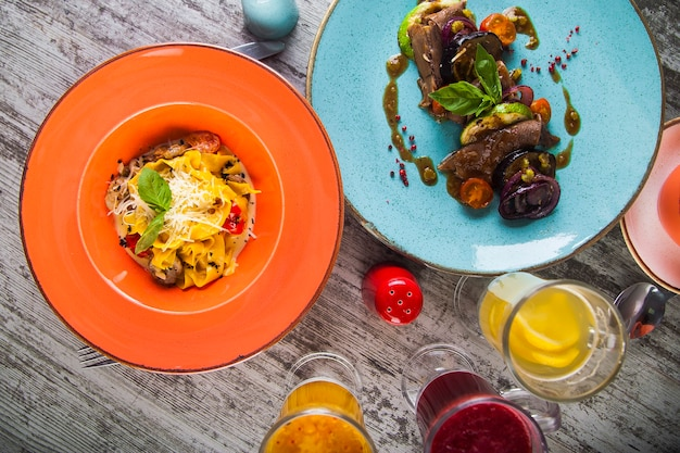 Lunch dishes and drinks from above on wooden background