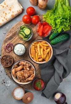 Обед, картофель, жареное мясо, овощи, лаваш и соусы на серой стене. ингредиенты для шаурмы, тако.