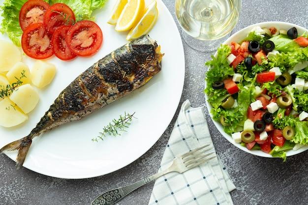 ランチ。じゃがいもと新鮮なサラダ、白ワイン、上面図と白い皿に揚げサバ