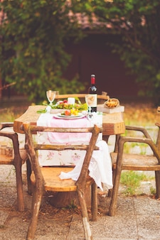 Lunch in the garden with wine and fruit. romantic dinner in the open air. autumn leaves of flowers. beautiful table scrapbooking. vintage photo.