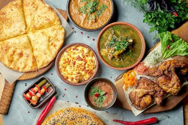Обед по грузинскому столу с харчо, лобио, курицей тапака, хачапури. вид сверху