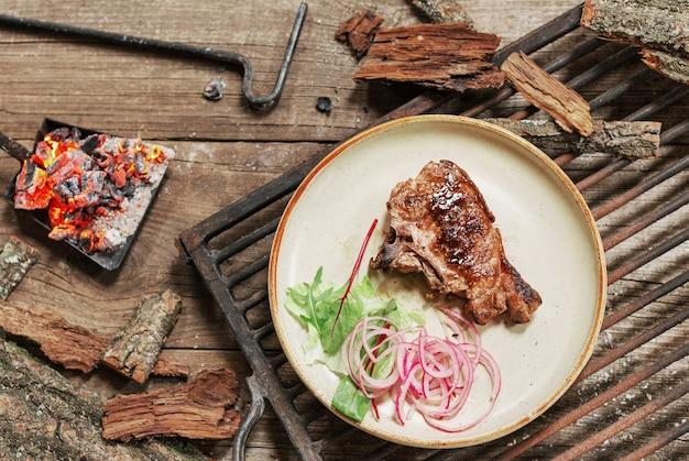 Обед на гриле из свинины на деревянном столе в деревенском стиле. bbc food.