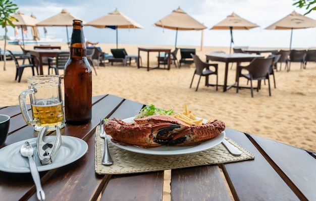 Обед в пляжном ресторане с вареной крабовой раковиной, картофелем фри, салатом на белой тарелке и холодным светлым пивом