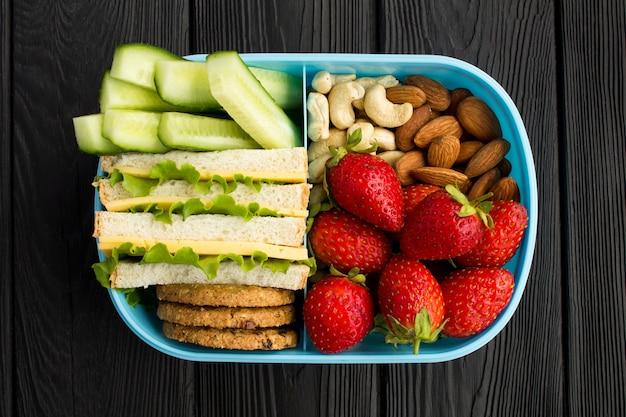 黒い木の中央にある青いボックスで昼食 Premium写真