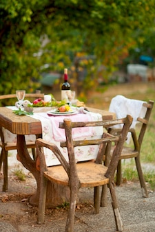 Lunch is romantic in autumn garden, atmosphere of holiday and coziness. autumnal dinner in the open air with wine and fruit. decor table with flowers and pomegranate.