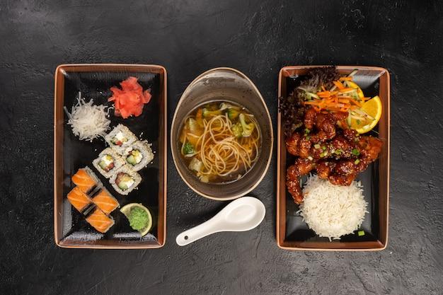 Обеденное меню из горячего мясного блюда с рисом, овощного супа с яичной лапшой и суши-роллов с лососем, имбирем, васаби и редисом дайкон.