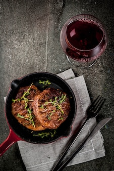 Lunch for one person. homemade grilled beef steaks with thyme in a portioned frying pan, with a fork, knife and a glass of wine.  on black stone table,  top view