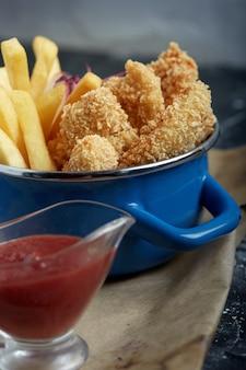 Обед или закуска - жареные куриные полоски и картофель фри на металлической сковороде с томатным соусом. крафт-бумага на фоне.