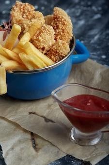 Обед или закуска - жареные куриные полоски и картофель фри на металлической сковороде с томатным соусом. крафт-бумага на месте.