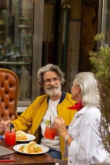 점심을 먹습니다. 행복한 남편과 아내는 거리 카페 테이블에 함께 앉아 식사를 하고 이야기를 나눴습니다.