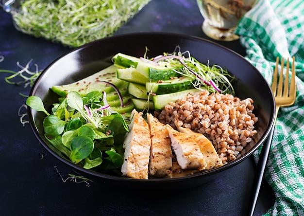 점심 샐러드. 메밀 죽, 구운 치킨 필레, 옥수수 샐러드, 마이크로 그린, 무를 곁들인 부처 그릇. 건강한 음식.