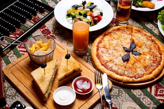 Настройка обеда с пиццей маргарита клуб сэндвич греческий салат и сок