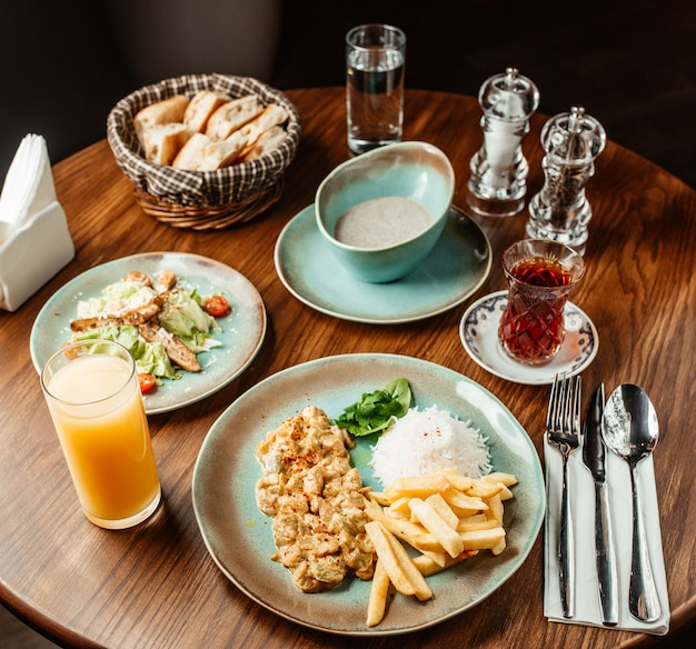 Lunch setup with mushroom soup creamy chicken dish with rice and fries caesar salad