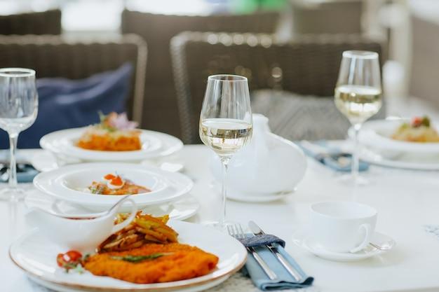레스토랑에서 차 세트와 음식과 화이트 와인 잔과 함께 점심 식탁보. 초점은 유리에 있습니다.